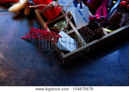 Preparation for Christmas. Wooden tray with ribbons, Christmas tags, on an old wooden table with vintage feel. Shallow depth of field.