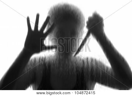 Shadowy figure with a knife behind glass