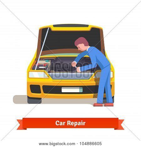 Car mechanic repairs engine at car service station