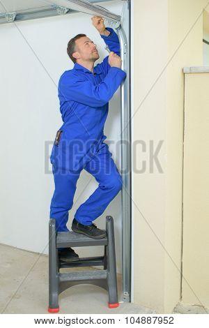 Man repairing a garage door frame