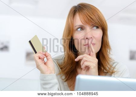 Woman deliberating, holding credit card