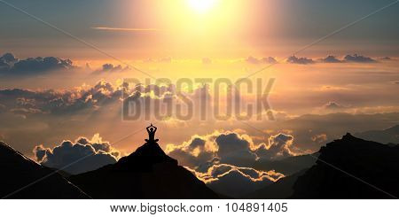 Practicing yoga outdoors. A person is sitting on the top of the hill at the sunset in Lotus pose.
