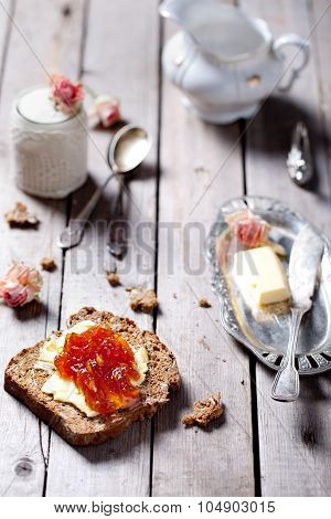 Piece of bread with butter and orange jam and rose flavor yogurt on a wooden table poster