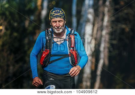 beautiful smiling senior man years running through woods