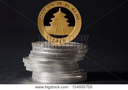 Chinese Gold Pand Coin On Top Of Silver Coins