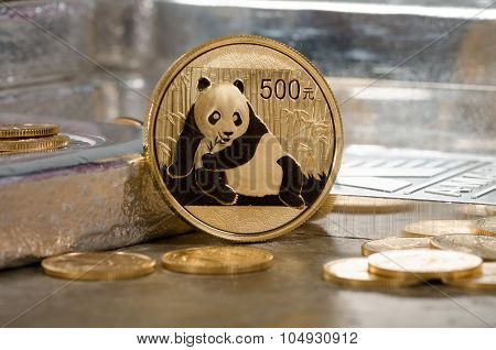 Chinese Gold Panda Coin With Silver Bars In Background