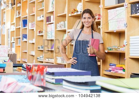Portrait of confident saleswoman with hand on hip holding book in store