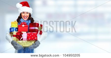 Beautiful Santa helper christmas girl with  gifts over blue background.
