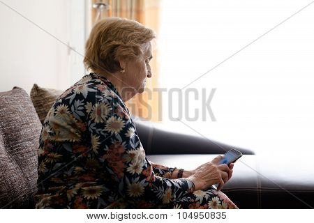 Elderly Woman Sitting At Home With Mobile Phone