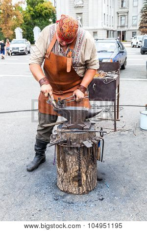 Blacksmith Handles The Horseshoe On The Anvil At The Outdoors