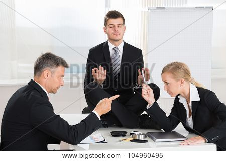 Businesspeople Quarreling In Front Of Businessman Meditating
