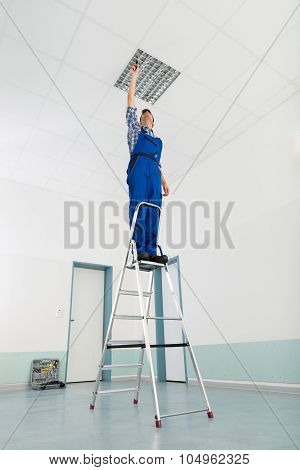 Male Electrician On Stepladder Installing Ceiling Light poster