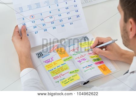 Close-up Of Businessman With Calendar Writing Schedule In Diary poster