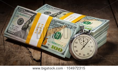 Time is money loan concept background - panorama of stopwatch and stack of new 100 US dollars 2013 edition banknotes (bills) bundles on wooden background