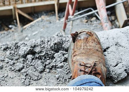 Old safety boots with construction site at background