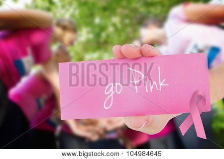 The word go pink and young woman holding blank card against smiling women running for breast cancer awareness