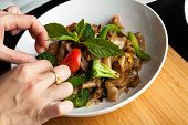 Food stylist grooms a dish by adding sweet basil garnish to the traditional thai dish Pad Kee Mao drunken noodle. poster