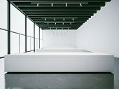 Empty white gallery interior with concrete floor and panoramic windows, black ceiling poster