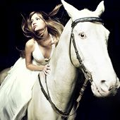 Beautiful blonde in a white dress on a white horse poster
