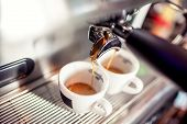Espresso machine pouring fresh coffee into cups at restaurant. Coffee automatic machine making coffee poster