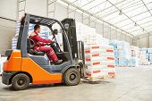 warehousing. Forklift driver stacking pallets with cement packs by stacker loader poster
