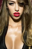 Portrait of glamour sexual charming pretty young woman with long hair red lips healthy and perfect skin looking straight dressed in black with deep decollete closeup vertical picture poster