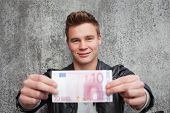 Attractive young guy holding ten euro note poster