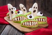 Funny halloween eadible monsters scary food healthy vegetarian snack dessert recipe for party decoration. Homemade spooky cyclop apples with teeth and banana ghosts on vintage wooden background. Natural treat poster