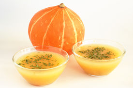 Two bowls of hot pumpkin soup and pumpkin on white background