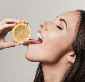 Close Up Portrait Of Young Woman  Eating Lemon