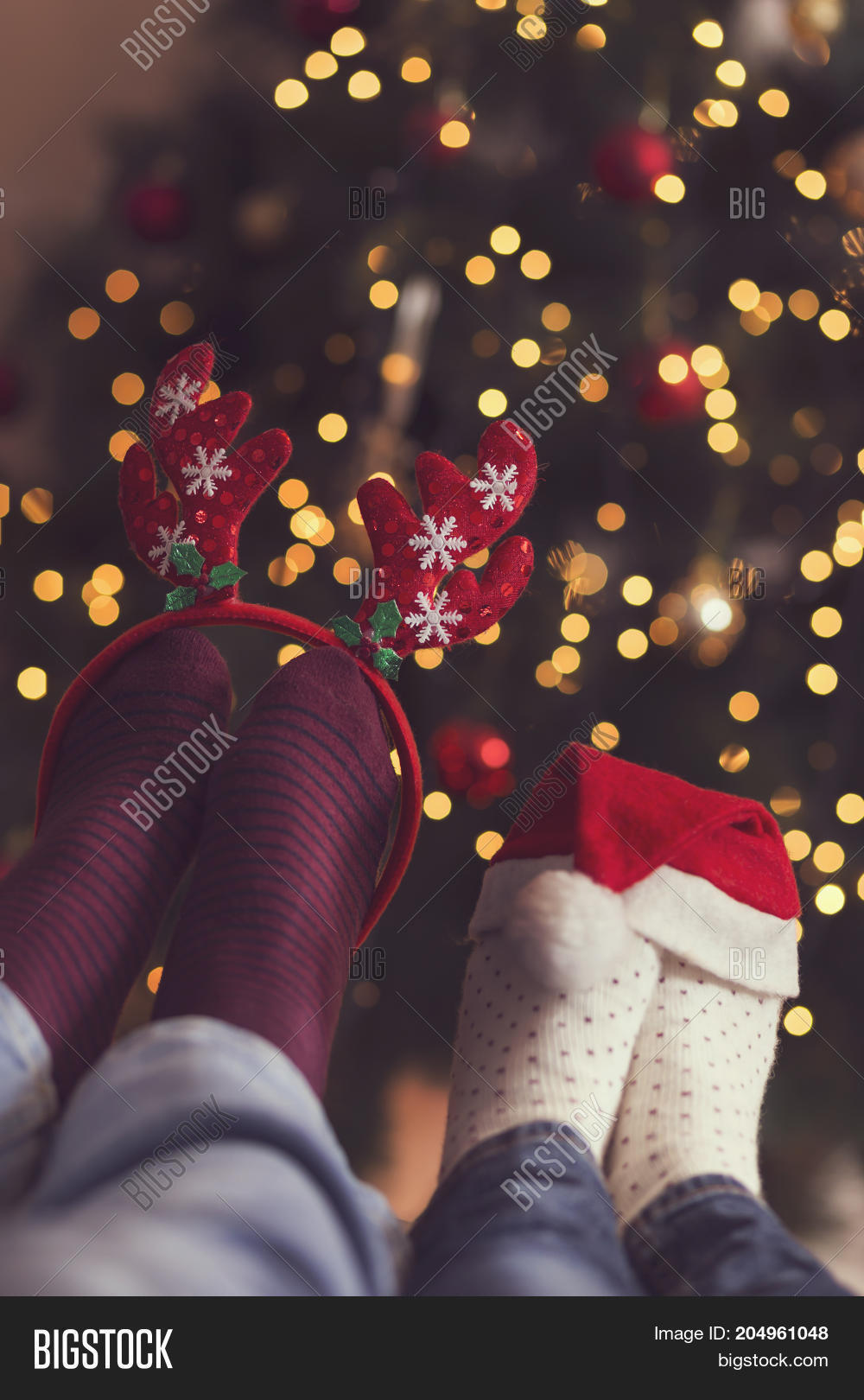 e8f1e294b52 Detail of male and female feet wearing warm winter socks with small Santa s  hat and antlers