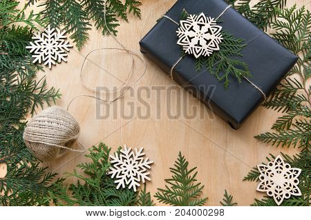 Christmas gift box wrapped in black paper around branch cypress with decor snowflakes on wooden surface. Copy space top view.