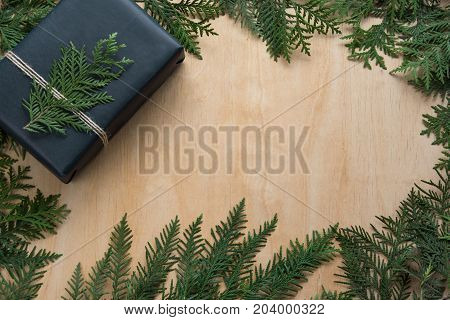 Christmas gift box wrapped in black paper with decor around branch cypress on wooden surface. Rustic style. Copy space.