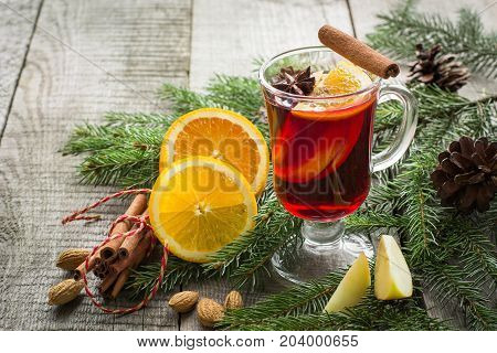 Christmas hot mulled wine with cinnamon orange and christmas tree on board. Close up. Winter tradition drink.