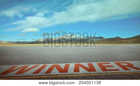 View of the empty asphalt road with winner word and beautiful mountain landscape . Evening scene .