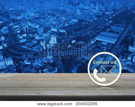 Telephone and mail icon button on wooden table over aerial of modern city tower street and expressway Contact us concept