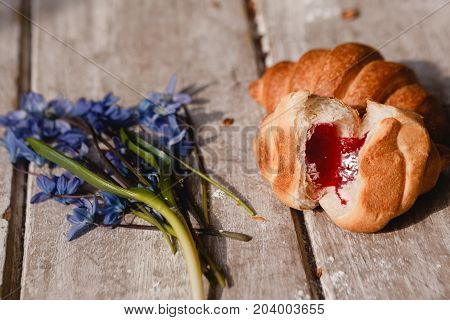 Delicious croissant on wooden background. Sweet breakfast with fruit jam and spring blue snowdrops nearby. Morning fresh and tasty meal. Food photography close up