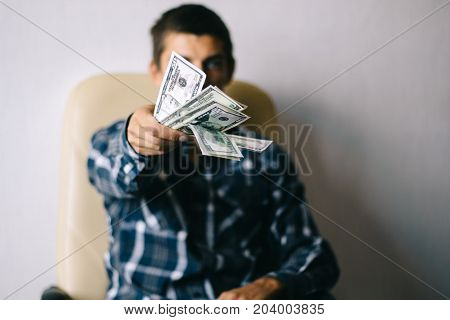 a young man in a chair  throws money (dollars)