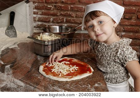 Little girl preparing pizza on the professional kitchen of old italian pizzeria. Adding cheese to pizza.