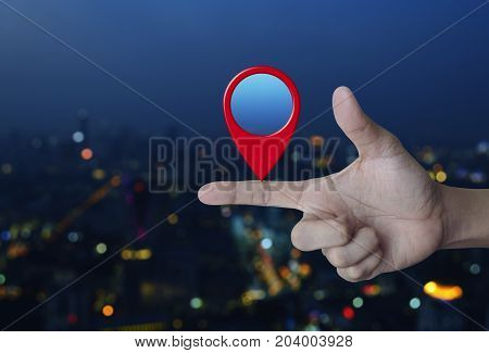 Map pin location button on finger over blur colorful night light city tower Map pointer navigation concept