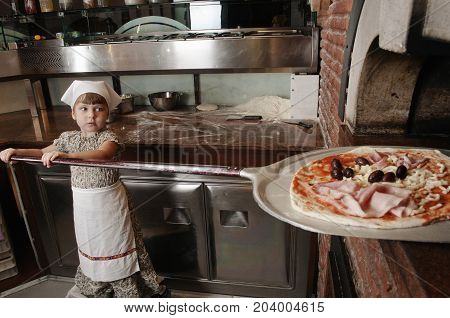 Baby baker puts pizza on the shovel into the wood-burning stove