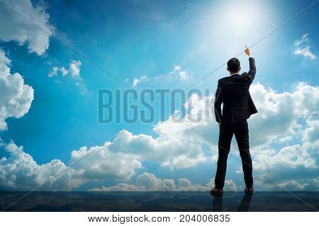 Back of successful businessman pointing up with his finger standing on top of building with sunlight sky background. Young man reaching goals success and achievement concept. Copy space.