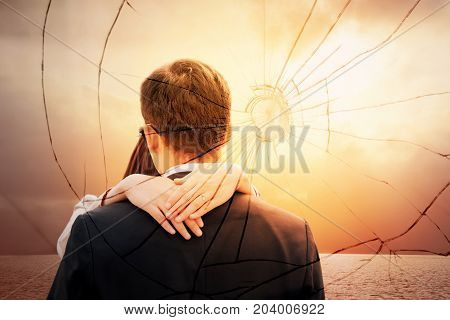 Lovers back hugging over dramatic sunset sky background.Sad young couple in relationship difficulties. Broken heart or divorce concept double exposure. Break off withdraw disengage one's engagement
