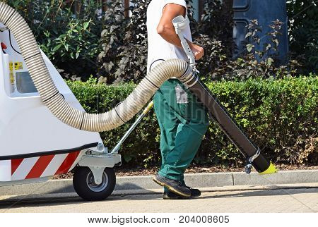 Street cleaner works with a vacum cleaner on the street