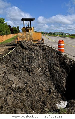 An front end loading machine with a bucket is pushing first to fill a hole on a sidewalk  and road construction project.