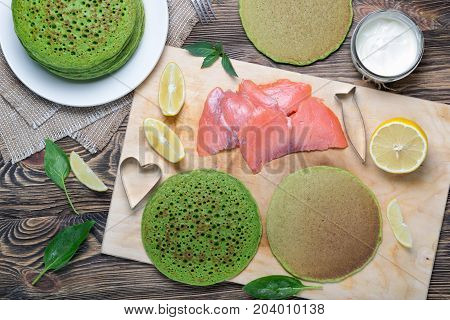 The process of making Breakfast pancakes with spinach with salmon. Stack of pancakes of spinach. On the table along with the fish, spinach and lemon wedges. Top view. Flat lay