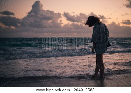 Silhouette Of A Girl Walking On The Ocean Coast