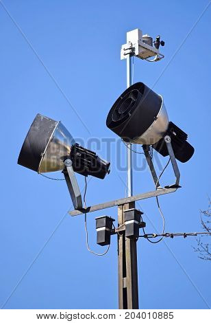 Reflectors on a high pole against blue sky