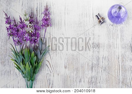 Flowers perfume bouquet on white wooden background isolation