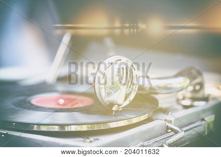Stylized view of a vintage gramophone with a needle on a black plate with a red sticker